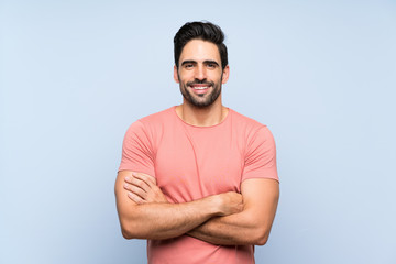 Handsome young man in pink shirt over isolated blue background keeping the arms crossed in frontal position Wall mural