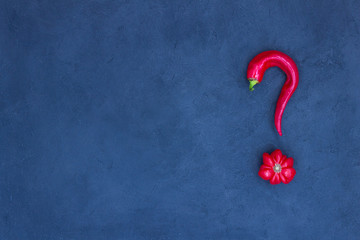Abstract picture of tomato and pepper in the shape of a question mark. Blue background. There is a place for text