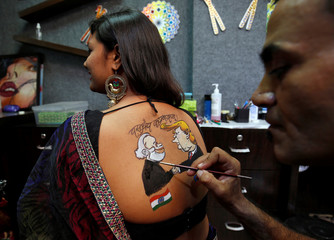 An artist applies final touches to a body paint tattoo sketched on the back of a woman in preparations for the upcoming Navratri in Ahmedabad