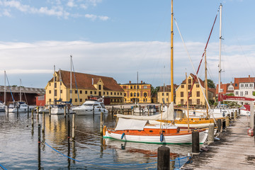 Old sailingboats and huge warehouses in the harbour of Svendborg