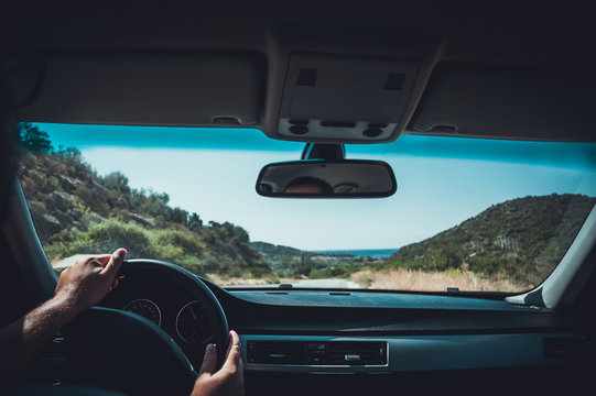 Freedom of the open road.Happy Driving on a Country Road in a Car with a sea in the view on the horizon.