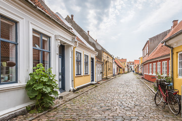 A red bike standing alone in an cobblestone street with romantic houses on the island Aero