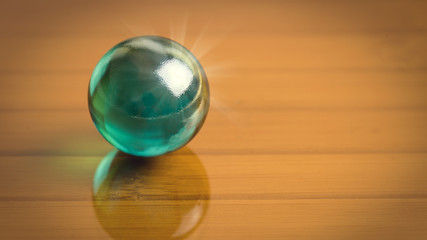 Dark green glass sphere on the reflect dark glass surface. Free place for your text or image. Abstract high resolution macro photography with 16:9 proportion useful for web design and decor.