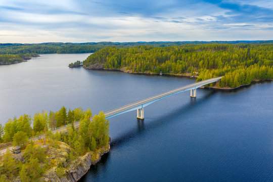 Aerial view of the bridge and island on a blue lake Saimaa. Landscape with drone. Blue lakes, islands and green forests from above on a cloudy summer morning. Lake landscape in Finland.