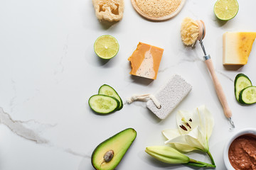 top view of natural soap pieces, body brush, loofah and pumice stone near fresh flower, lime, cucumber and avocado on marble surface Wall mural