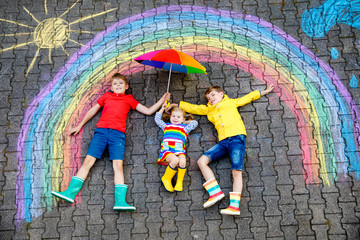 three little children, two school kids boys and toddler girl having fun with with rainbow picture drawing with colorful chalks on asphalt. Siblings in rubber boots painting on ground playing together.