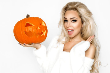 Surprised woman with beautiful face and blond hair holding pumpkin in studio on white background. Halloween concept - Image