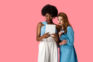 pretty redhead girl holding credit card near african american woman with digital tablet isolated on pink