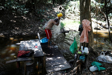 An employee washes himself in Bom Retiro deforestation area on the right side of the BR 319 highway near Humaita