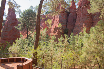 Ochre Trail in Roussillon, Sentier des Ocres, hiking path in a natural colorful area of red and yellow cliffs surrounded by green forest in Provence