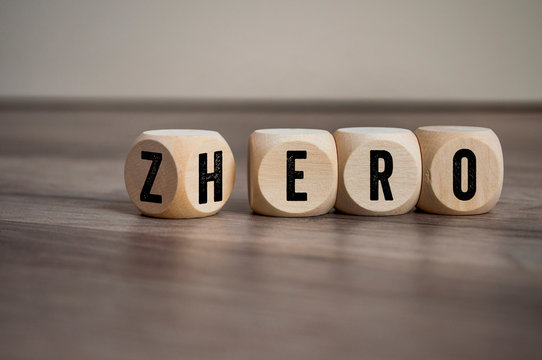 Cubes and dice with words from zero to hero on wooden background