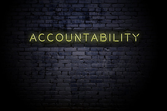 Highlighted brick wall with neon inscription accountability