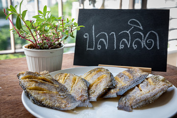 Thai food fried salid fish cut in stripes.  Trichogaster pectoralis on wooden background