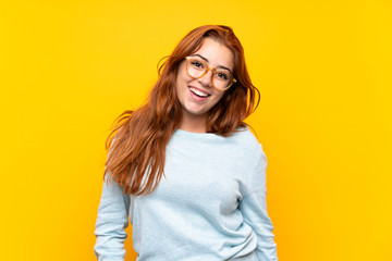 Teenager redhead girl over isolated yellow background with glasses and happy