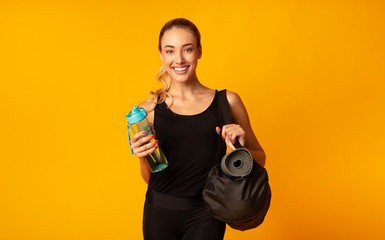 Keuken foto achterwand Fitness Positive Sporty Girl Holding Bag, Mat And Water, Yellow Background