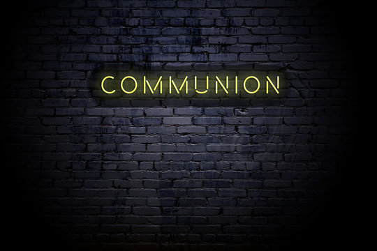 Highlighted brick wall with neon inscription communion
