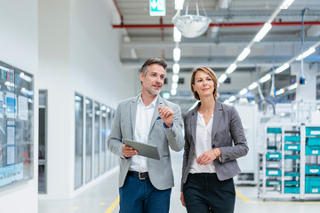 Businesswoman and businessman with tablet walking and talking in a modern factory
