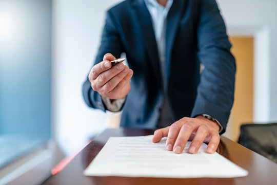 Close-up of businessman in office presenting ballpen and contract