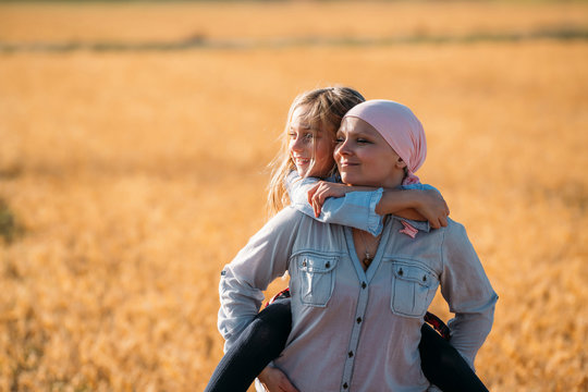 A woman with cancer carrying her daughter on her back, looking sideways