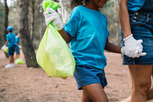 Woman and girl walking hand in hand collecting garbage in a park