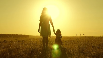 Mom walks on field with her little daughter in sunset. baby holds mom's hand, happy family walks in evening out of town. mother and baby are resting in park. child plays with mother in meadow.
