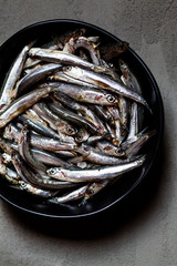 Directly above view of fresh anchovies in bowl on concrete