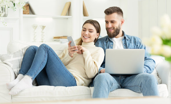 Millennial woman showing something on phone to husband
