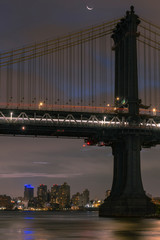 Manhattan Bridge from the East river at night with moon in a crescent phase