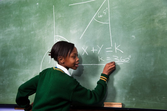 A young girl solving a math sum on a blackboard