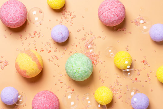 Colorful bath bombs, pink salt and soap bubbles on a pastel orange background, top view, flat lay. Spa concept, background.