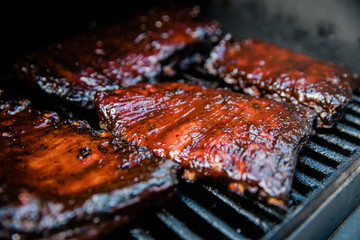Smoked Barbecue BBQ ribs on the smoker grill charred on the edges and covered in barbecue sauce homemade Wall mural