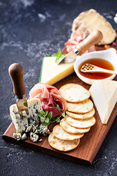 Cheese and snack board with crackers and prosciutto