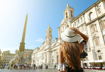Travel in Rome. Back view of beautiful girl visiting Piazza Navona square landmark in Rome on sunny day. Summer holidays in Italy.