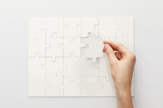 cropped view of woman completing jigsaw puzzle on white background
