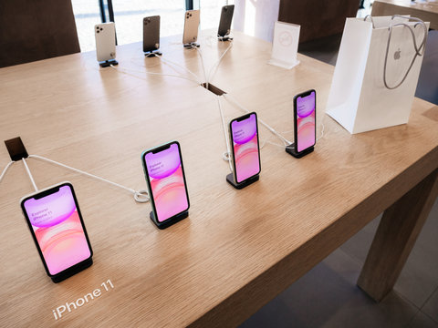 Paris, France - Sep 20, 2019: View from above of new iPhone 11 displayed in Apple Store as they goes on sale - white present shopping bag on wooden table corner