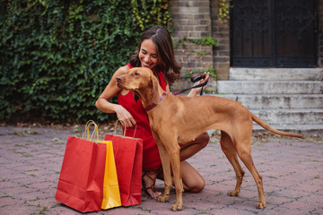 Young woman with her dog on the street after shopping in the city
