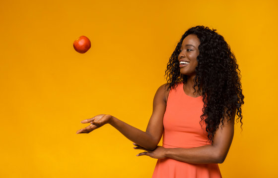 Female fitness model playing with red apple