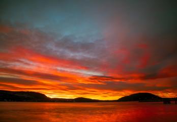 Różowo czerwony zachód słońca nad Drøbak w Norwegii