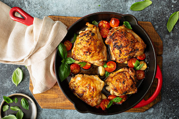 Chicken thighs roasted with tomatoes and garlic, quick dinner dishrecipe