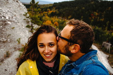 Loving couple takes a selfie against the backdrop of an autumn landscape. A man kisses a woman, a woman looks into the frame and smiles.