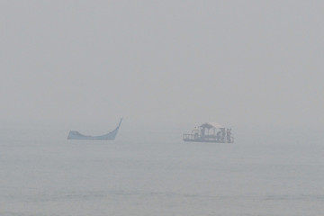People fish in smog due to the forest fire in Pidie