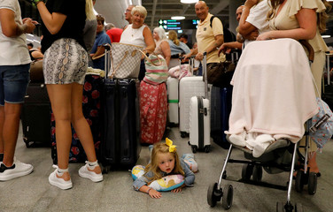 A 3 years old British passenger Indie Robertson lays on the ground as her family queue up at a check-in service at Dalaman Airport