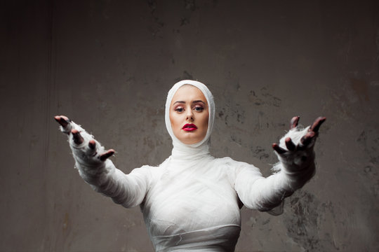 Beautiful young woman in bandages. Girl in a mummy costume, Pulling hand.