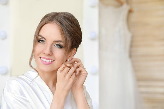 Beautiful young bride wearing earrings before wedding ceremony at home