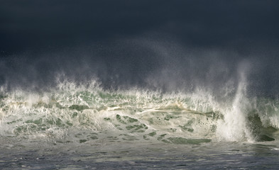 Seascape. Powerful ocean wave on the surface of the ocean. Wave breaks on a shallow bank. Stormy weather, stormy clouds sky background. Wall mural