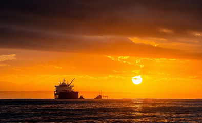 Fotorollo Rotglühen Oil tankers ship at sea on a background of sunset sky. Oil tankers in the ocean. Early in the morning, the sunrise sky. South Africa. Mossel Bay