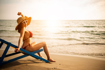woman relax on chair beach in vacations with sunrise background.Enjoy asian women and the coconut at the beach with morning light background