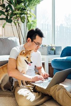 Man using laptop with dog