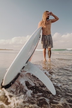 A young guy with dreadlocks is standing on the beach, looking at the waves and preparing to ride on the spot.