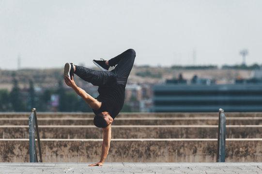 Young hispanic latin break dancer performing a dance pose in urban scenery